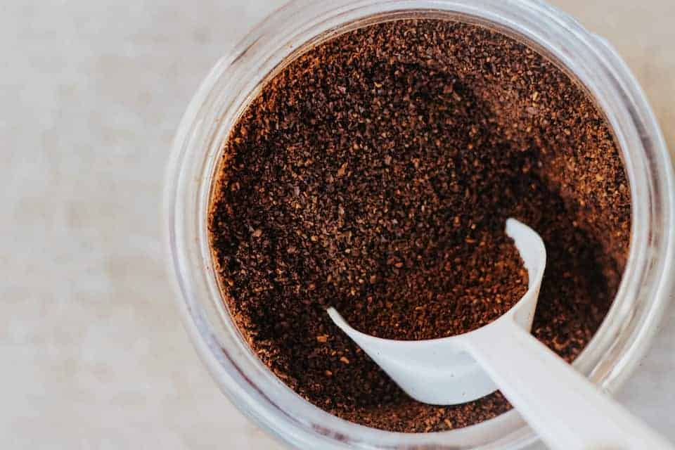 Ground coffee in a container with a scoop