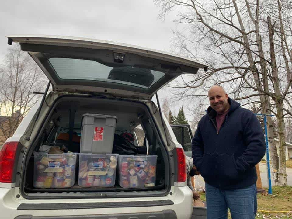man stands next to car loaded with food