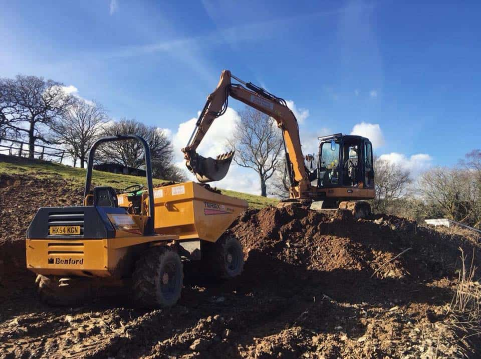 excavator and dumper moving ground in front of blue skies and clouds