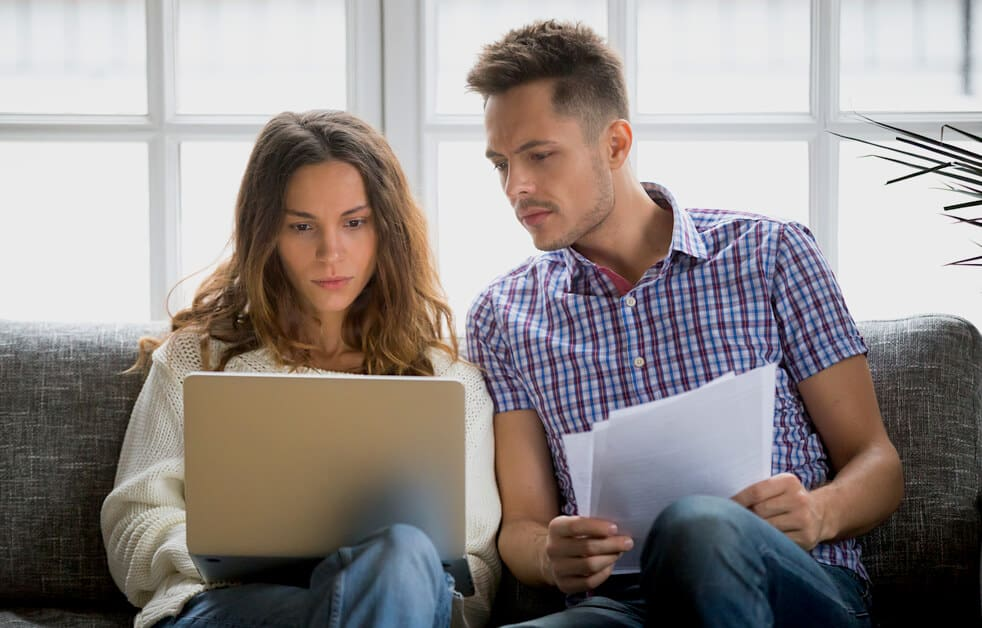 Couple Reading Home Insurance Policy For Claim