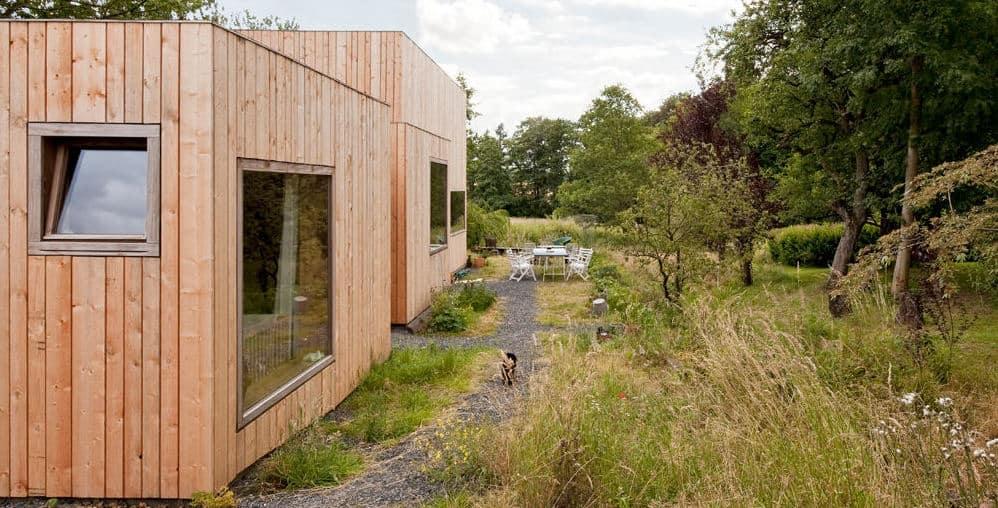 Das Bild zeigt ein Tiny House mit einer Baugenehmigung für dauerhaftes Wohnen auf einem schönen Grundstück mit Bäumen und Garten.