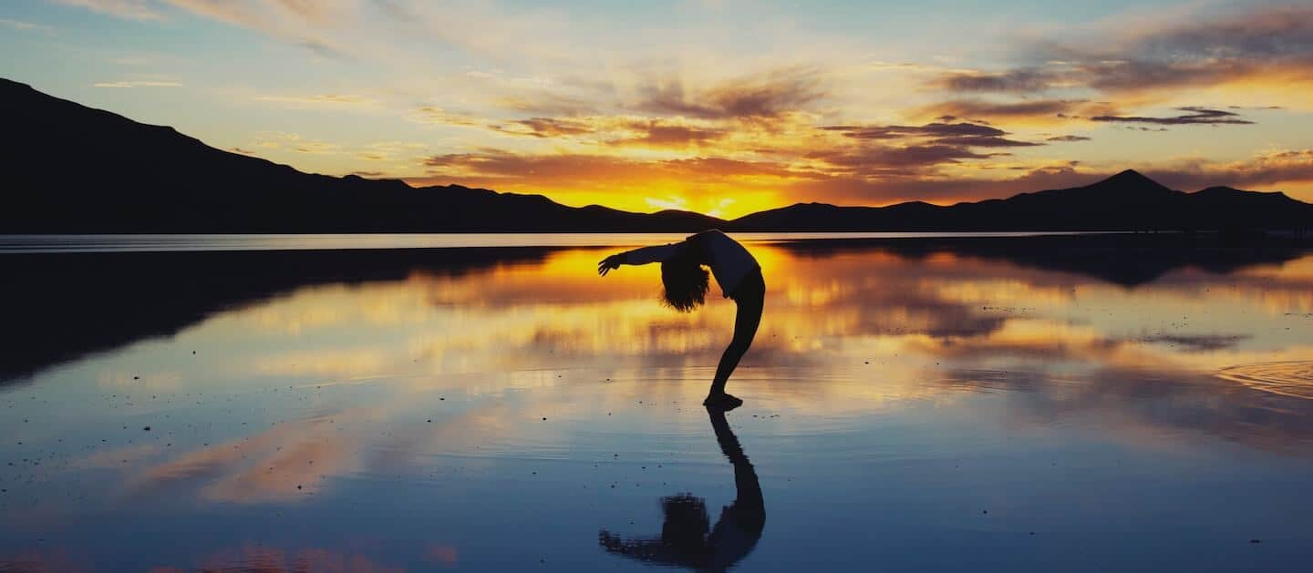 get your life back - girl stretching on beach after opiate detox