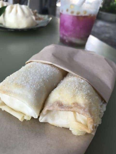 two pongu lumpia pineapple cream cheese spring rolls tucked into paper sack