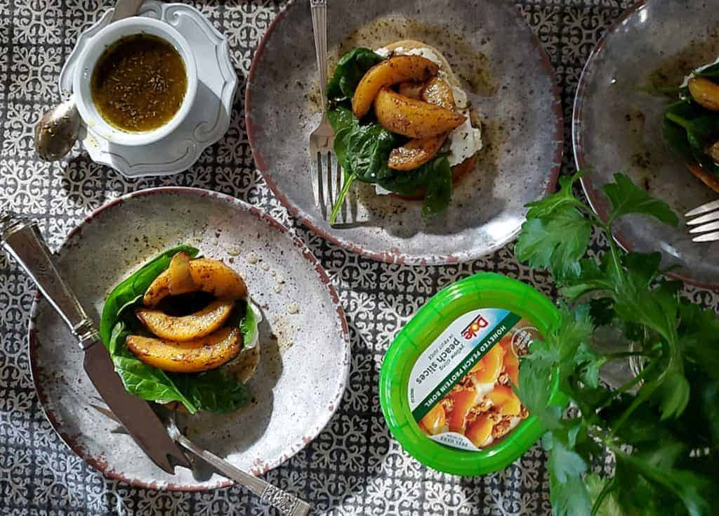 warm spiced peach spinach salad on toasted bagel
