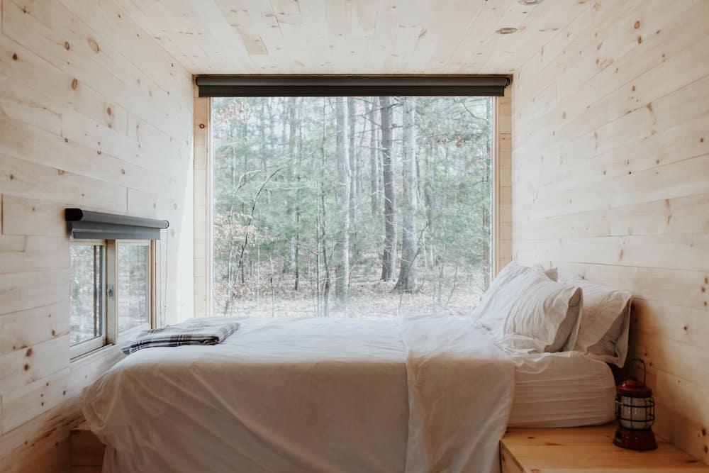 Das Bild zeigt ein Minihaus von Innen. Zu sehen ist ein Schlafzimmer mit einem großen Fenster