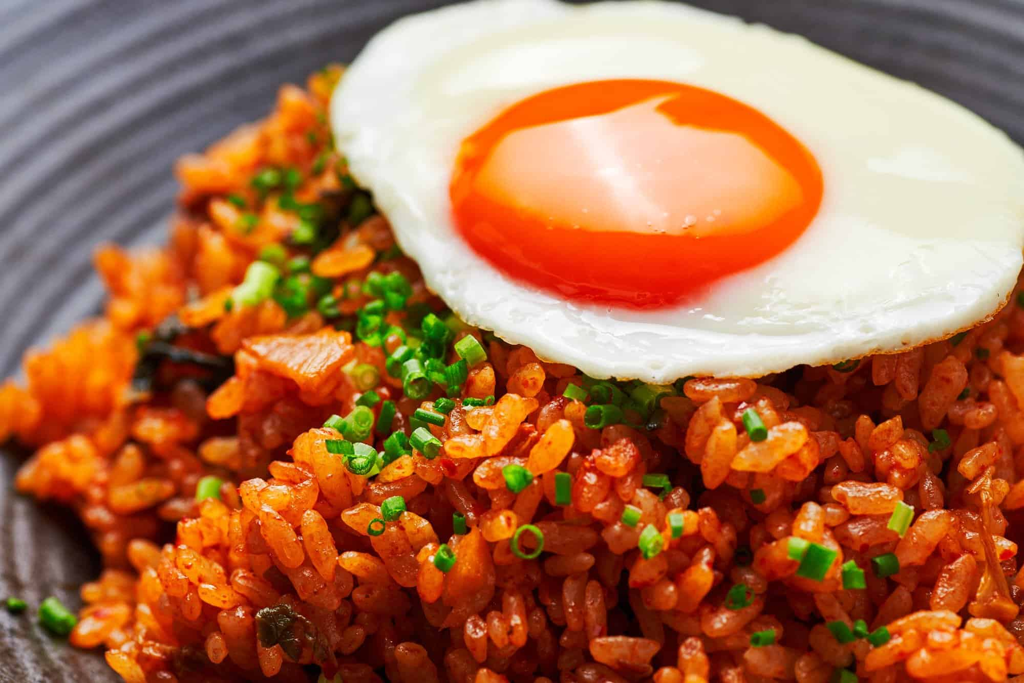 Sunny-side-up egg on top of a bowl of spicy kimchi fried rice, or kimchi bokkeumbap.