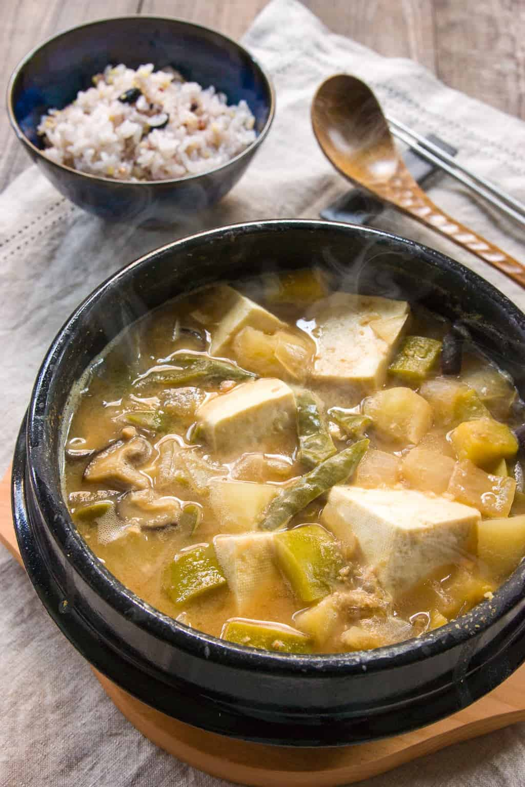 Doenjang Jjigae, is a hearty Korean stew loaded with vegetables, mushrooms and garlic and redolent of garlic. Seasoned with a fermented bean paste, it has an nutty funk that gives the soup a marvelous earthy flavor.