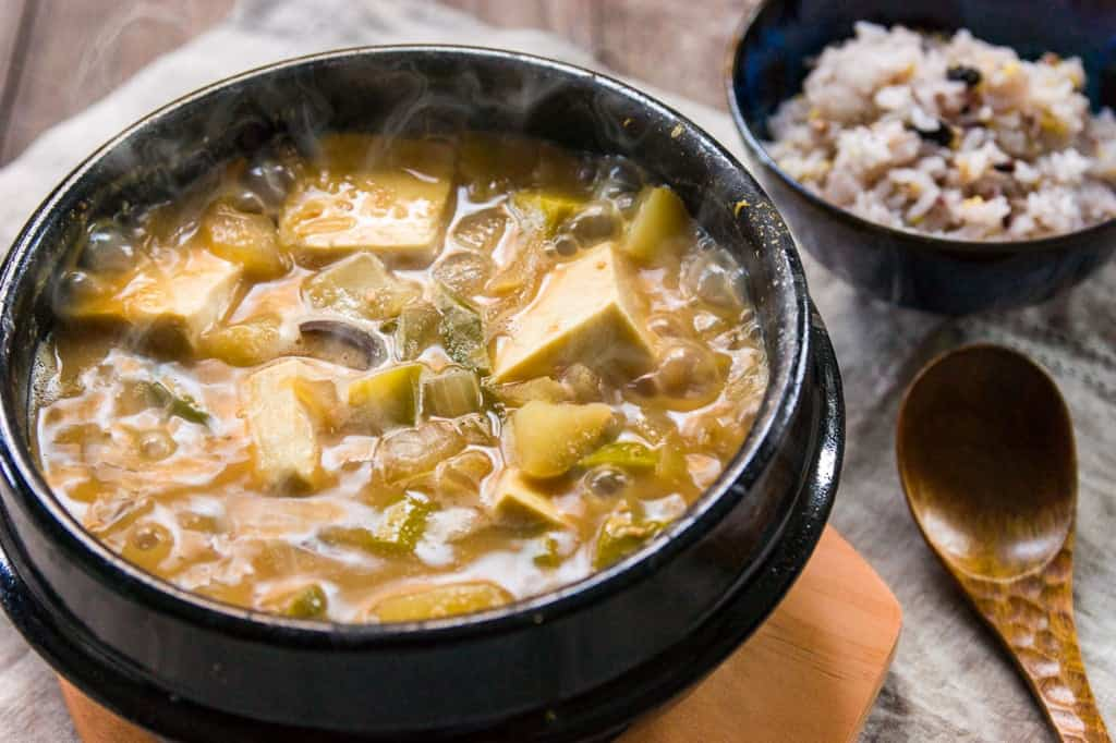 By serving doenjang jjigae in the earthenware pot it was boiled it it stays hot untl the last bite.