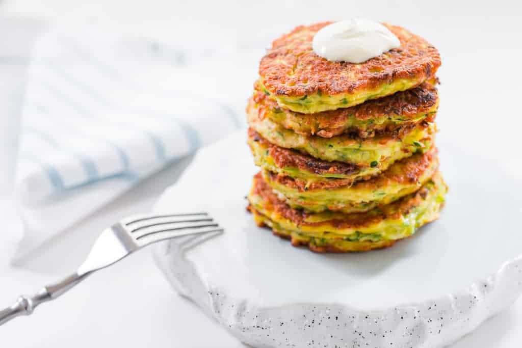 A stack of delicious zucchini pancakes with a dollop of sour cream.