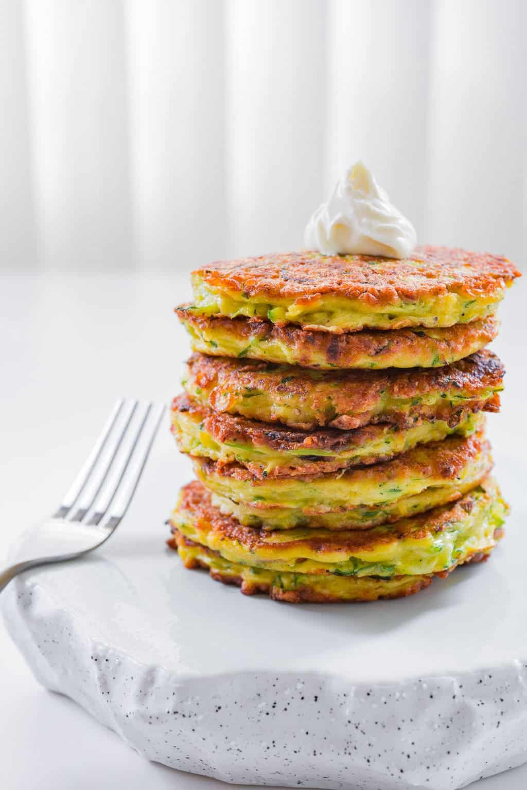 Fluffy zucchini pancakes with caramelized scallions and Gruyere cheese are tender, flavorful and delicious.
