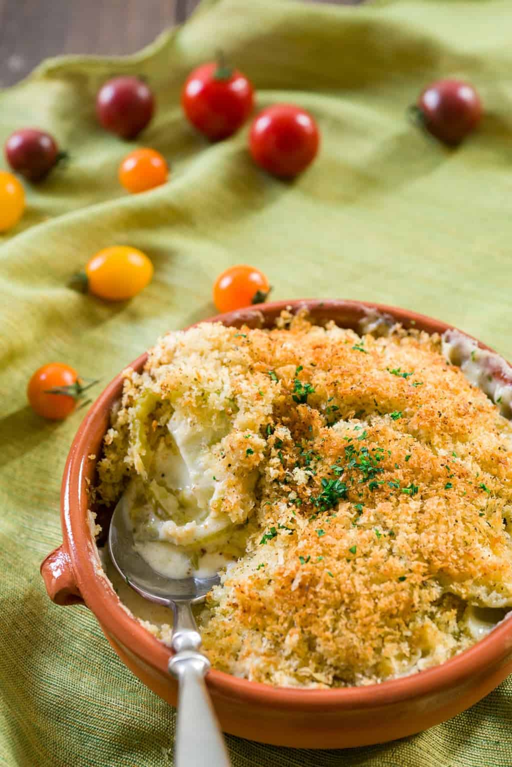 Tart tender green tomatoes are surrounded by a cheesy mornay sauce bubbling up from below in this Green Tomato Gratin. With a crisp panko and herb topping, this decadent side is addictively good.