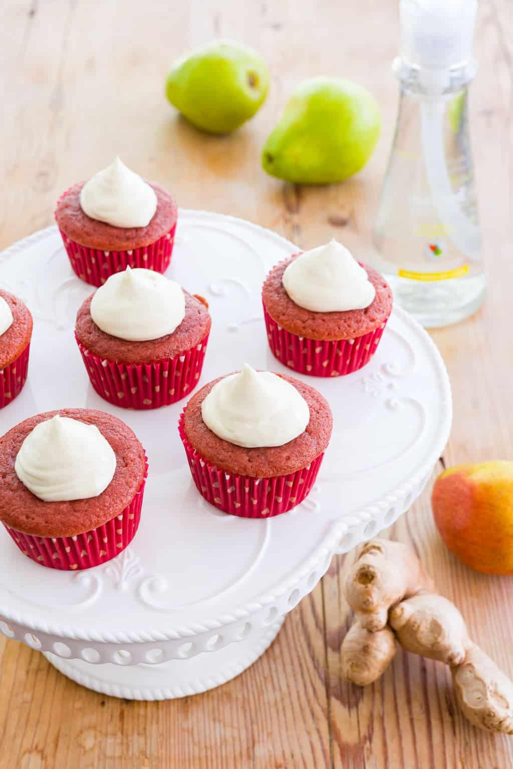 Red velvet cupcakes filled with caramel poached pear and topped with a ginger white chocolate cream cheese frosting.