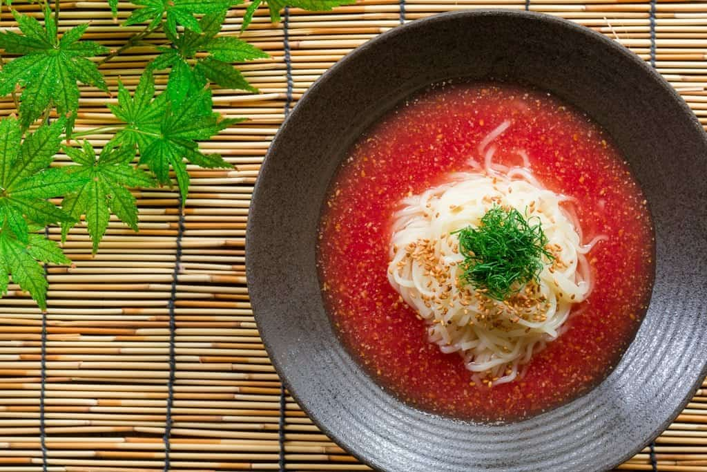 Chilled udon noodles in a savory tomato sesame broth, perfect for summer!