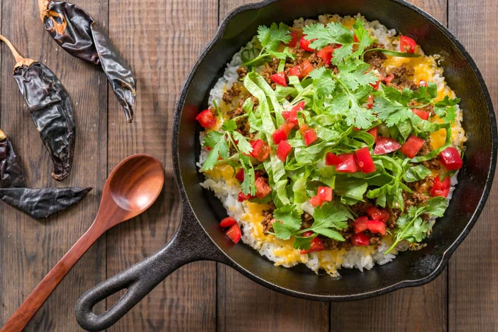 Taco Rice is a mashup of Japanese and Texmex cuisine with taco meat, cheese, lettuce and tomatoes on a bed of white rice.