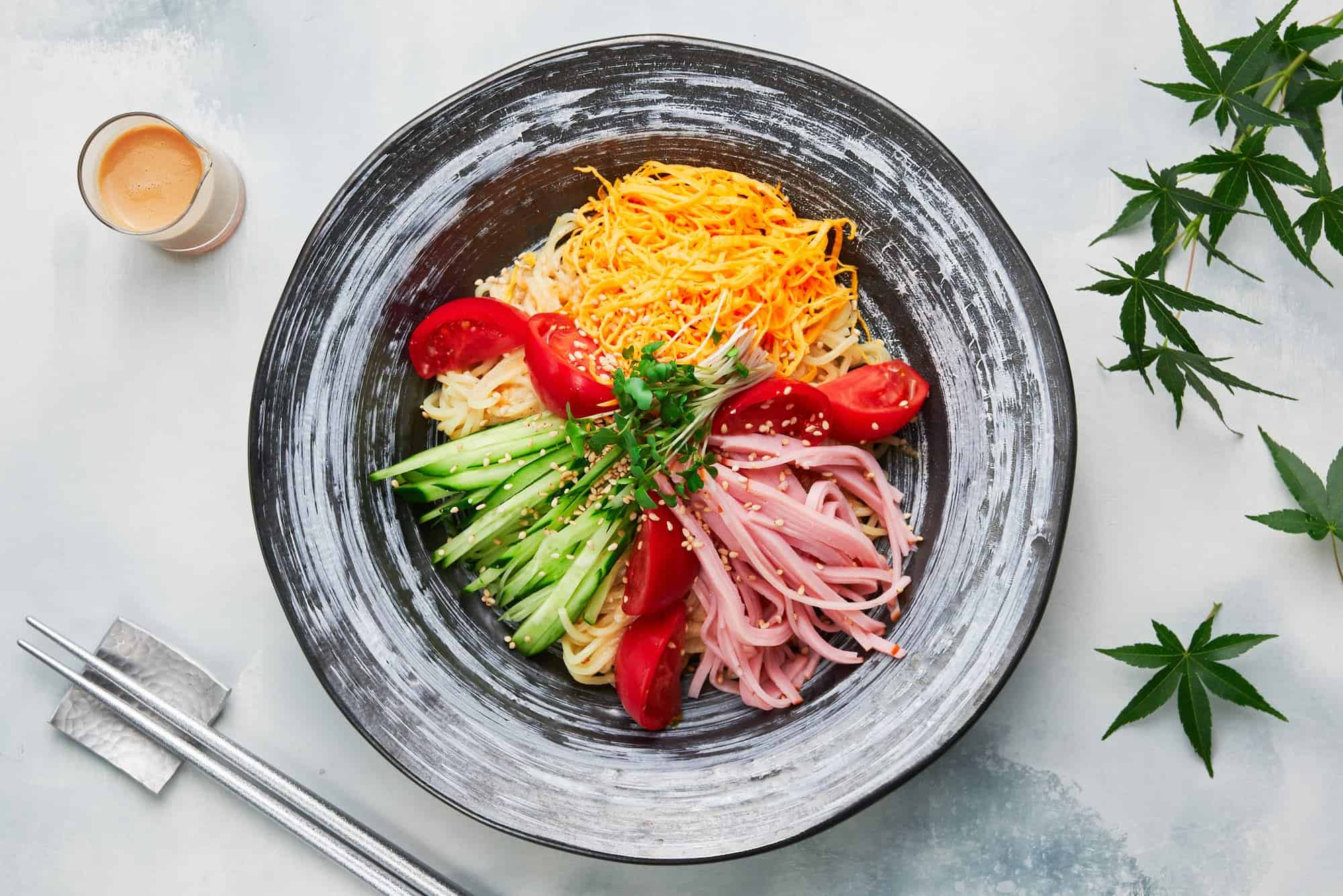 Topped with sweet tomatoes, crisp cucumbers, savory ham, and golden threads of egg, this easy ramen salad (hiyashi chuka) is the perfect summer meal.