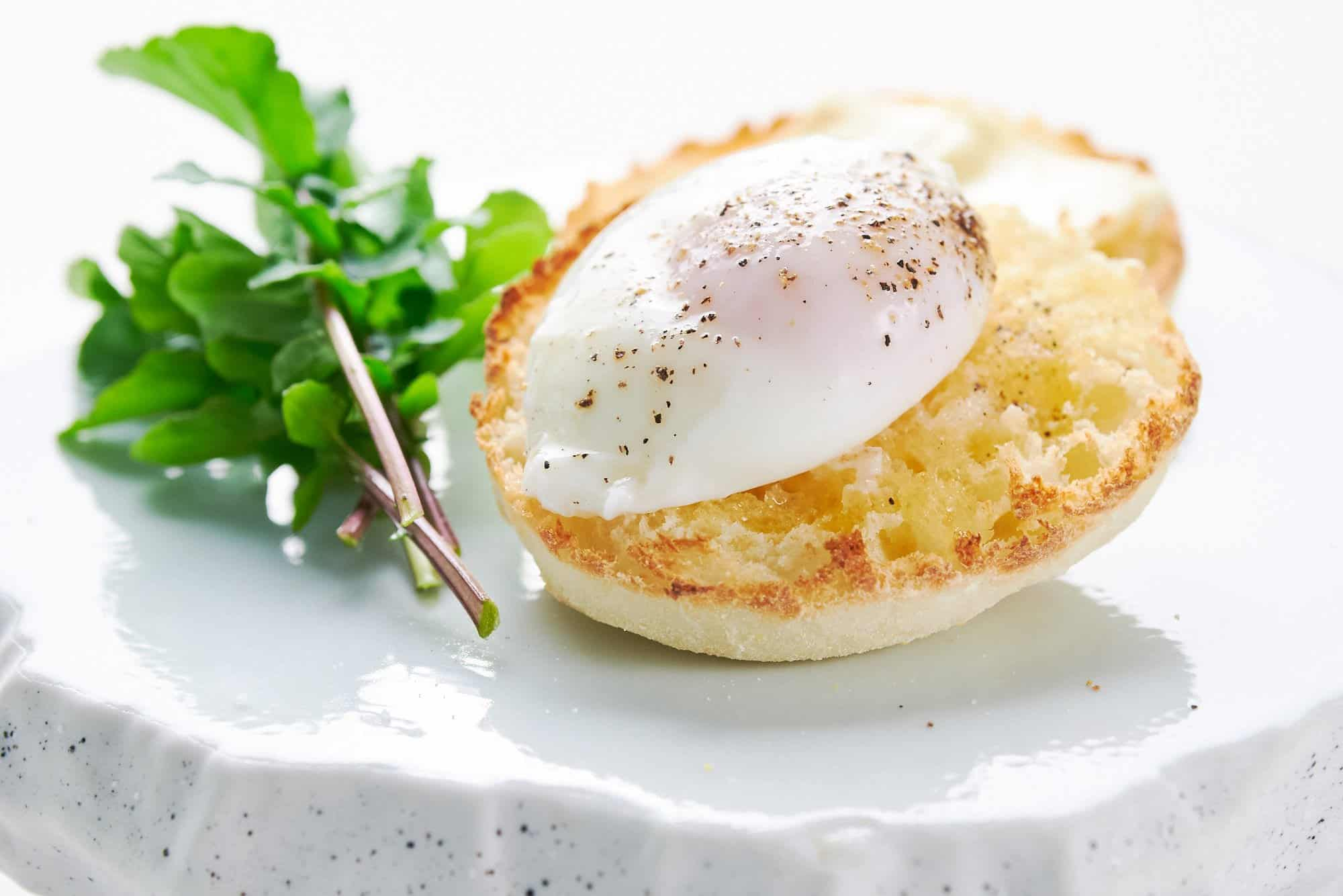 Perfect oval poached egg without whispy egg whites on toasted english muffin with arugula.