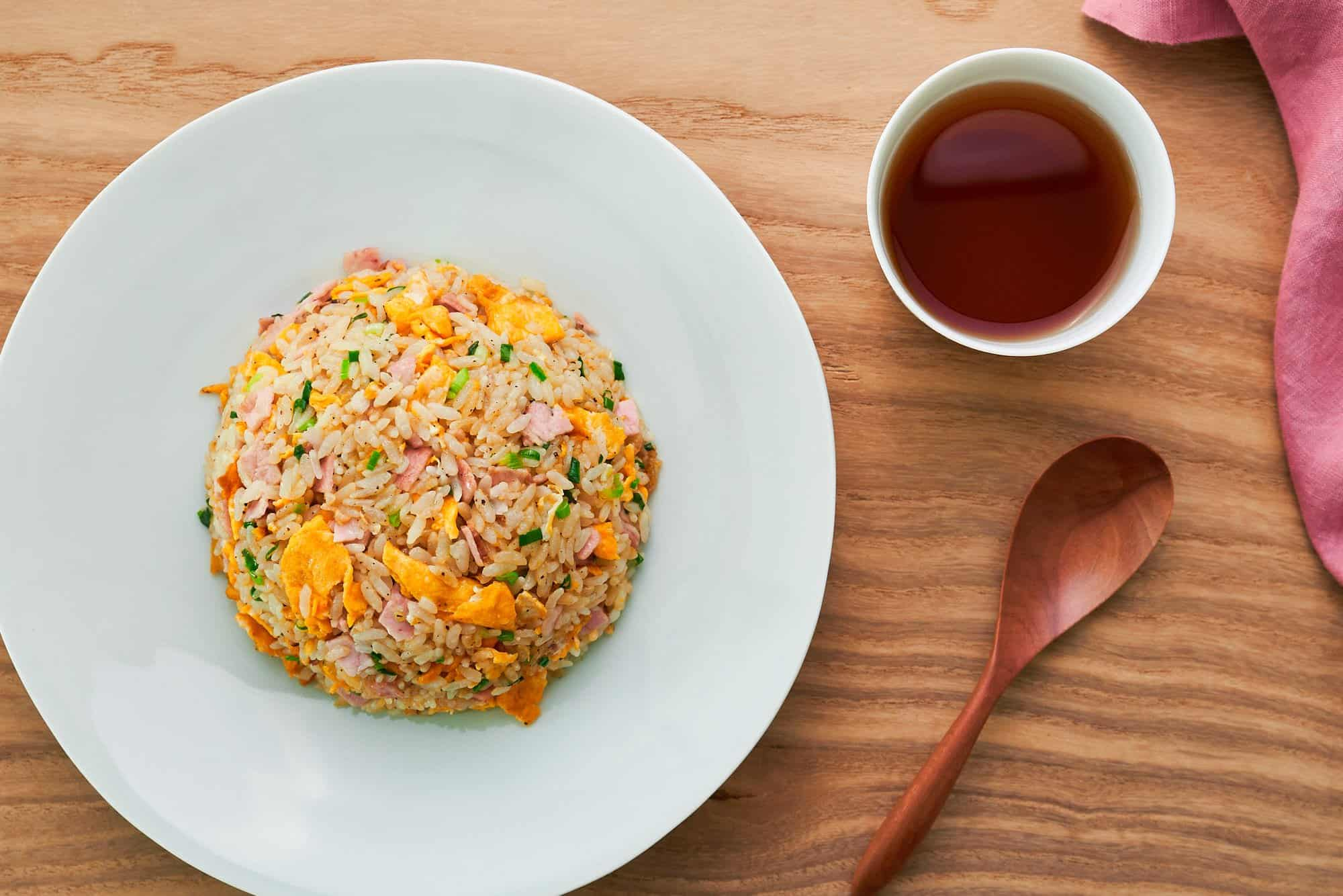 Yakimeshi (Japanese fried rice) on a white plate with barley tea and a wooden spoon.