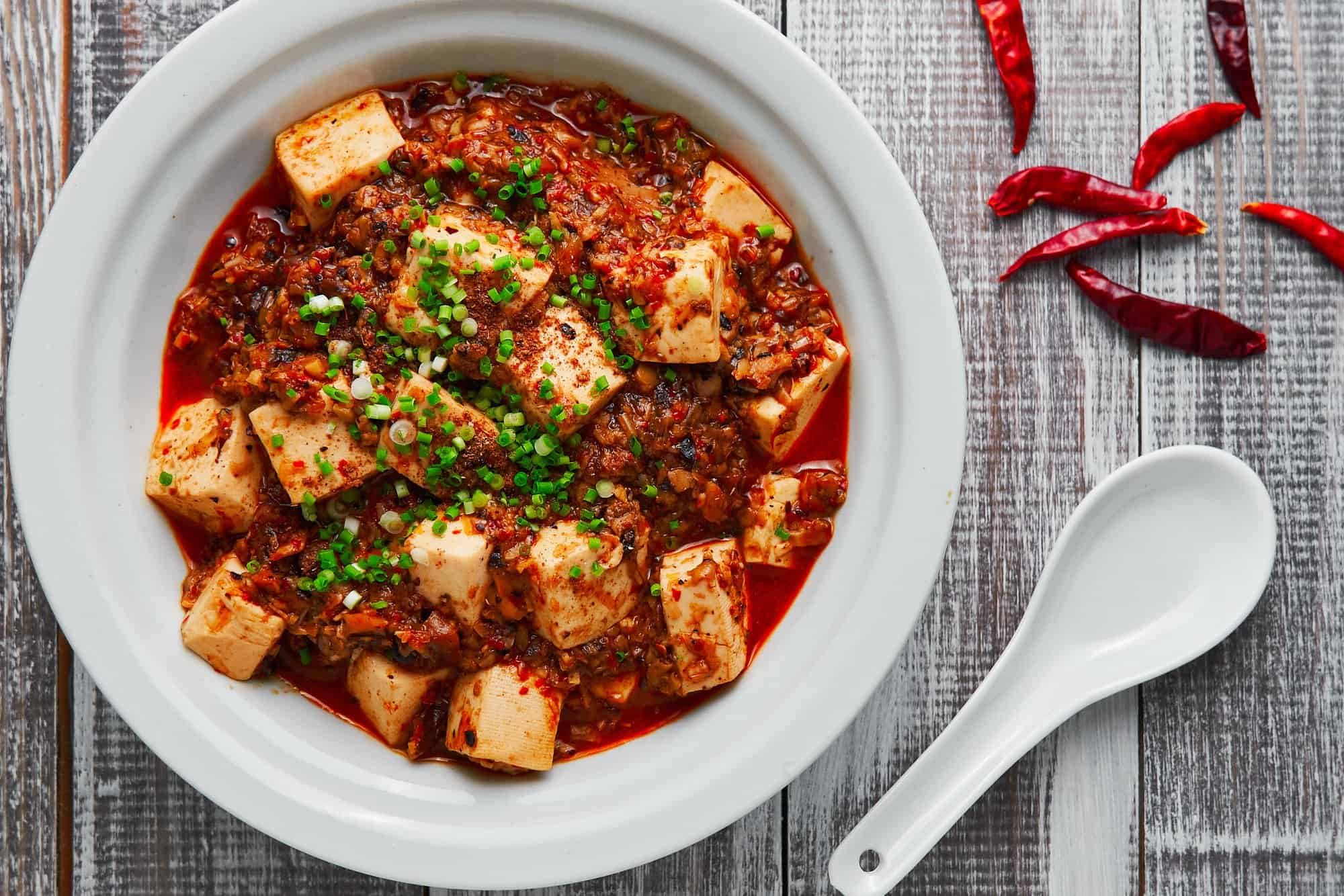 This Vegan Mapo Tofu is loaded with creamy blocks of tofu in a fiery Sichuan sauce made from ground mushrooms and fermented black soybeans.