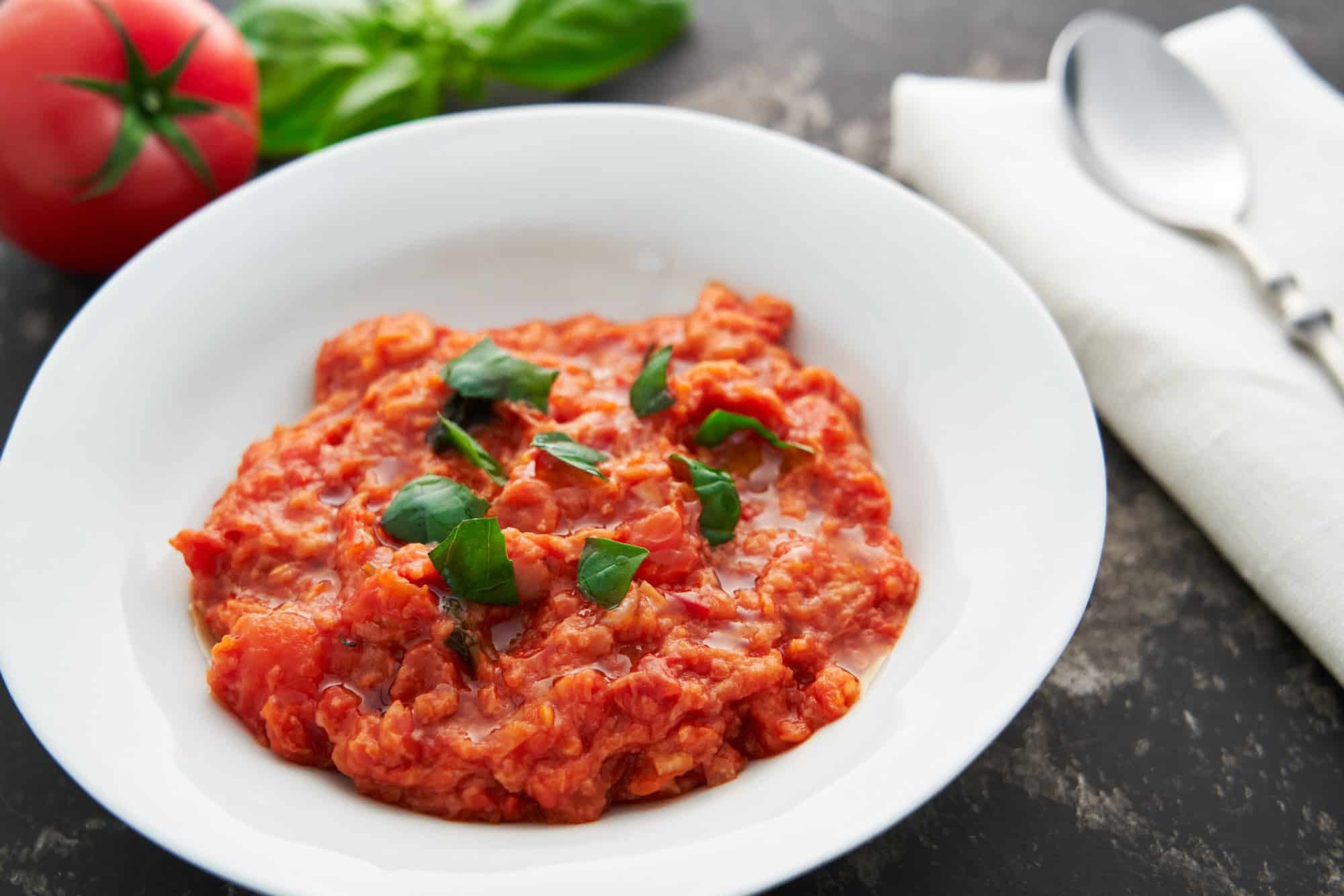 Pappa al Pomodoro, or Tuscan Bread and Tomato Porridge made with a flavorful tomato soup thickened with crusty bread, served with fresh torn basil and a drizzle of olive oil.