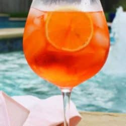 an aperol spritz next to a swimming pool.