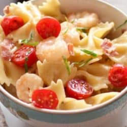 Shrimp and pasta in a bowl with tomatoes on top.