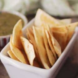 baked tortilla chips in a white dish next to a green napkin.