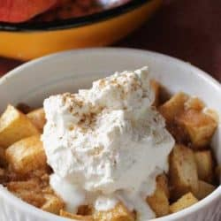 Apple Crisp with whipped cream on top served in a white ramekin
