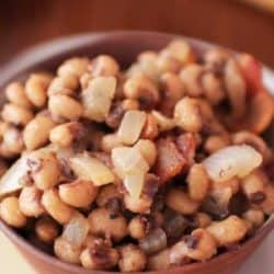 a brown bowl of black eyed peas on a brown table.