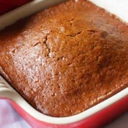 a mini gingerbread loaf in a red baking dish.