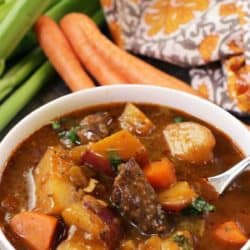 a bowl of stew filled with lamb, carrots and potatoes.