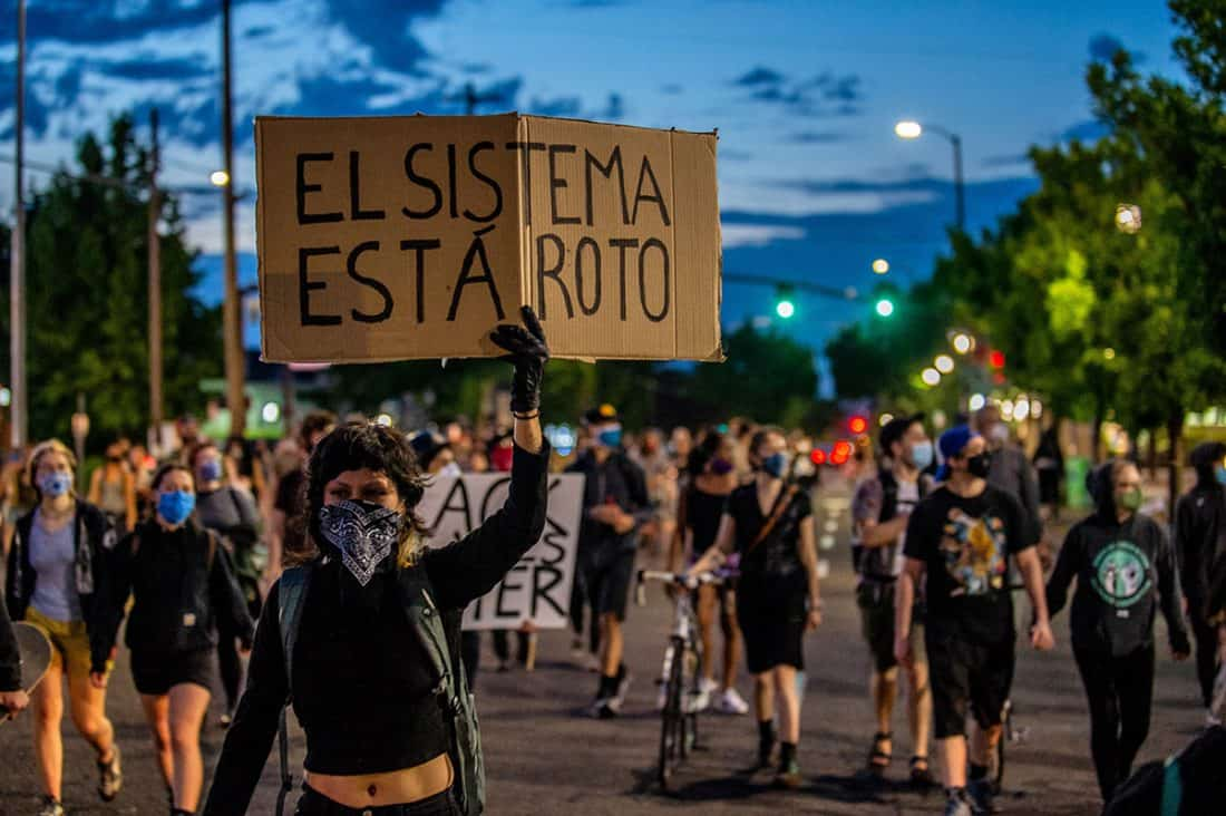 A crowd of marchers with dark blue evening sky behind them. The woman in front holds a sign reading EL SISTEMA ESTÁ ROTO.