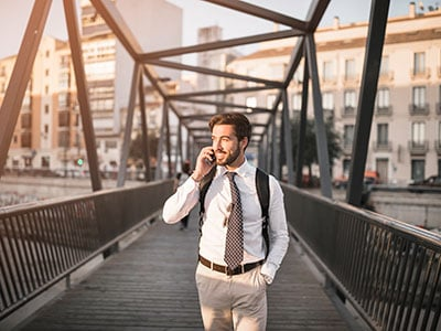 Business Man Using Mobile Integration to Talk on Cell Phone While Crossing Bridge