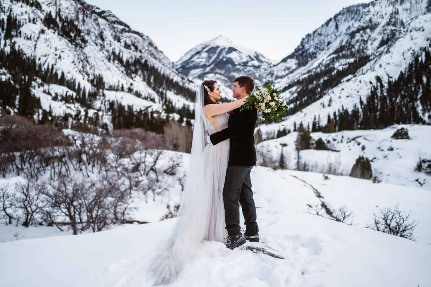 Bride and Groom Hugging in Snow Best Places to Elope in Colorado