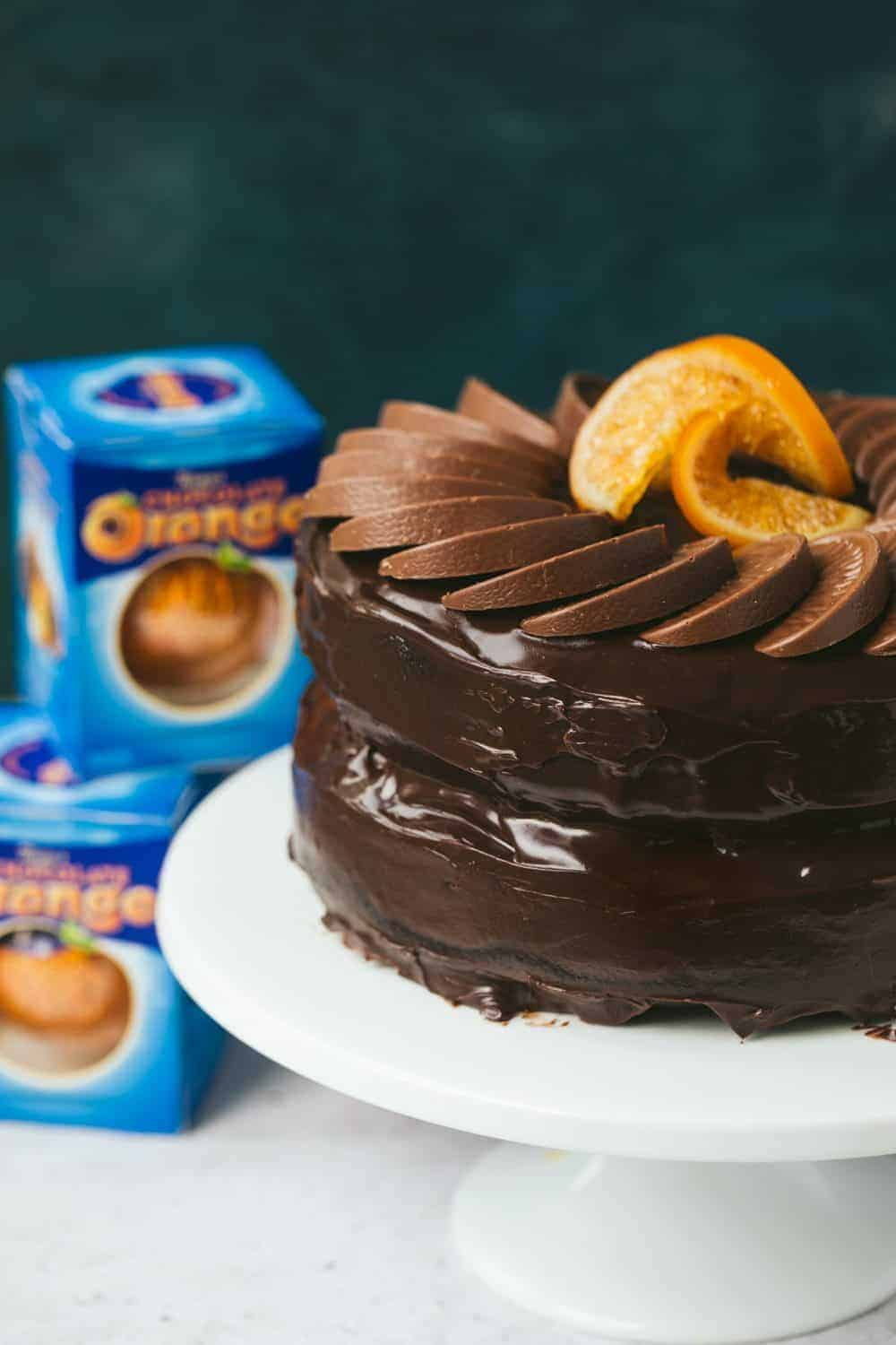 A chocolate orange cake topped with Terry's chocolate orange segments. There are 3 boxes of chocolate oranges visible in the background.
