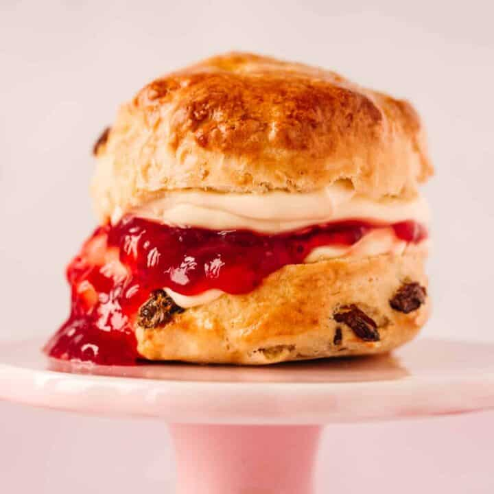 A small pink cake stand with a fruit scone on top. There is jam and clotted cream oozing out and dripping down the left side of the scone.