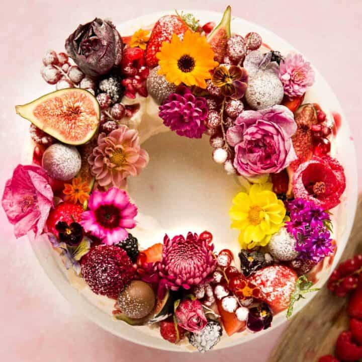 A pavlova wreath covered with whipped cream, berries, chocolates and edible flowers