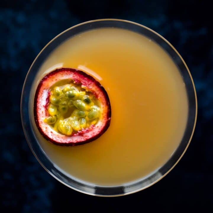 Overhead view of a pornstar martini with a slice of passionfruit floating on top.