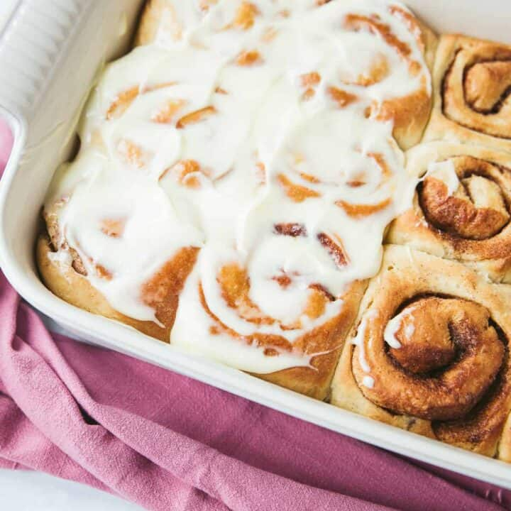 A white baking dish containing Cinnamon Rolls, half have been spread with cream cheese frosting and the other half have been left plain.