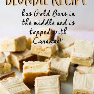 Pieces of white chocolate blondie on a serving board. Pinterest image with text overlay.