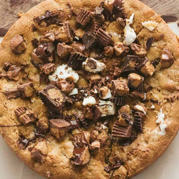 A peanut butter cookie pie covered with Reese's mini cups.