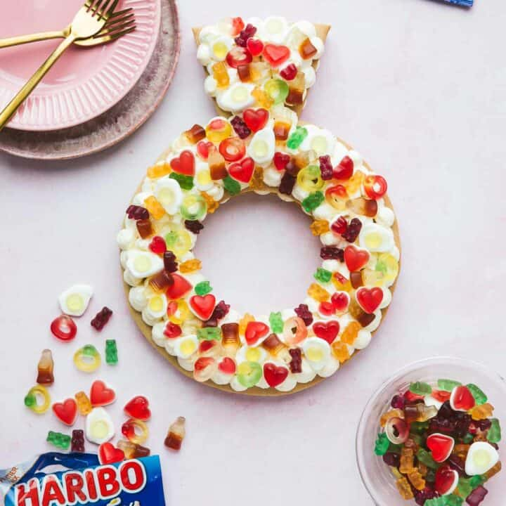 A cream Tart in a ring shape decorated with Haribo sweets.