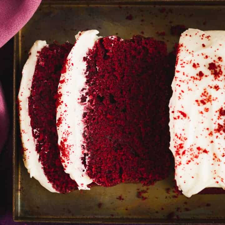 A moist red velvet cake, bright red in colour with a white coloured frosting.