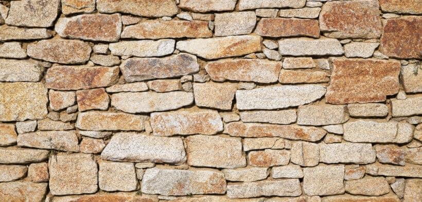 Eine Natursteinmauer kann dem Garten eine gemütliche Atmosphäre verleihen