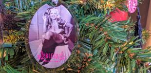 Close-up of ornament featuring b/w photo of Jennie Lee in Santa's helper outfit, hanging on a lit Christmas tree