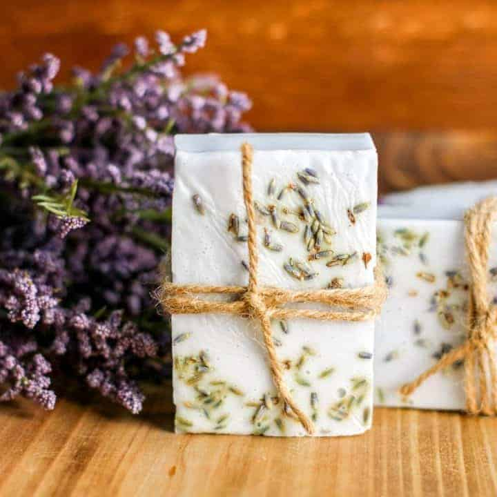 bar of lavendar soap tied with jute twine on cutting board with fresh lavendar