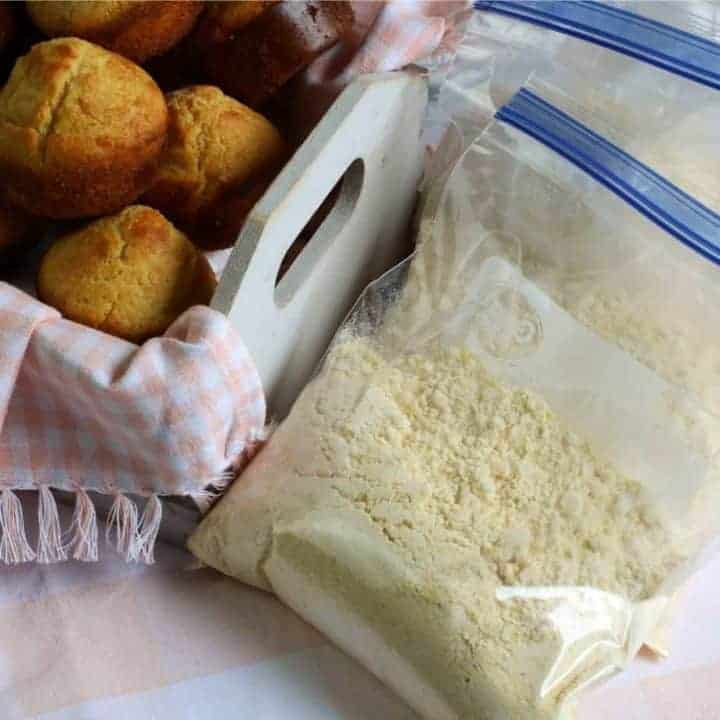 square image of cornbread mix in plastic storage bags and white basket of corn muffins