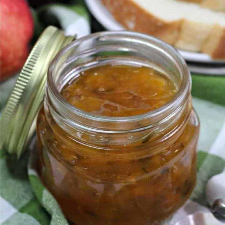 jar of peach jalapeno jam on green and white cloth napkin