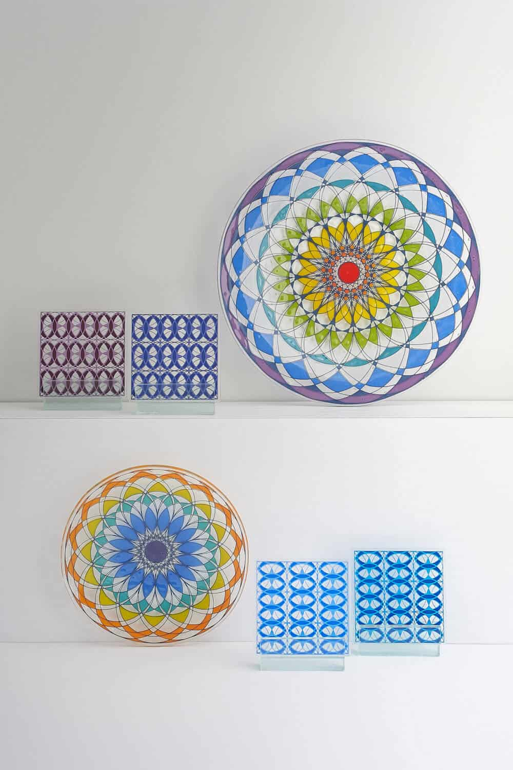 Softly lit group product image of glassware pieces including geometric plates and glass coasters