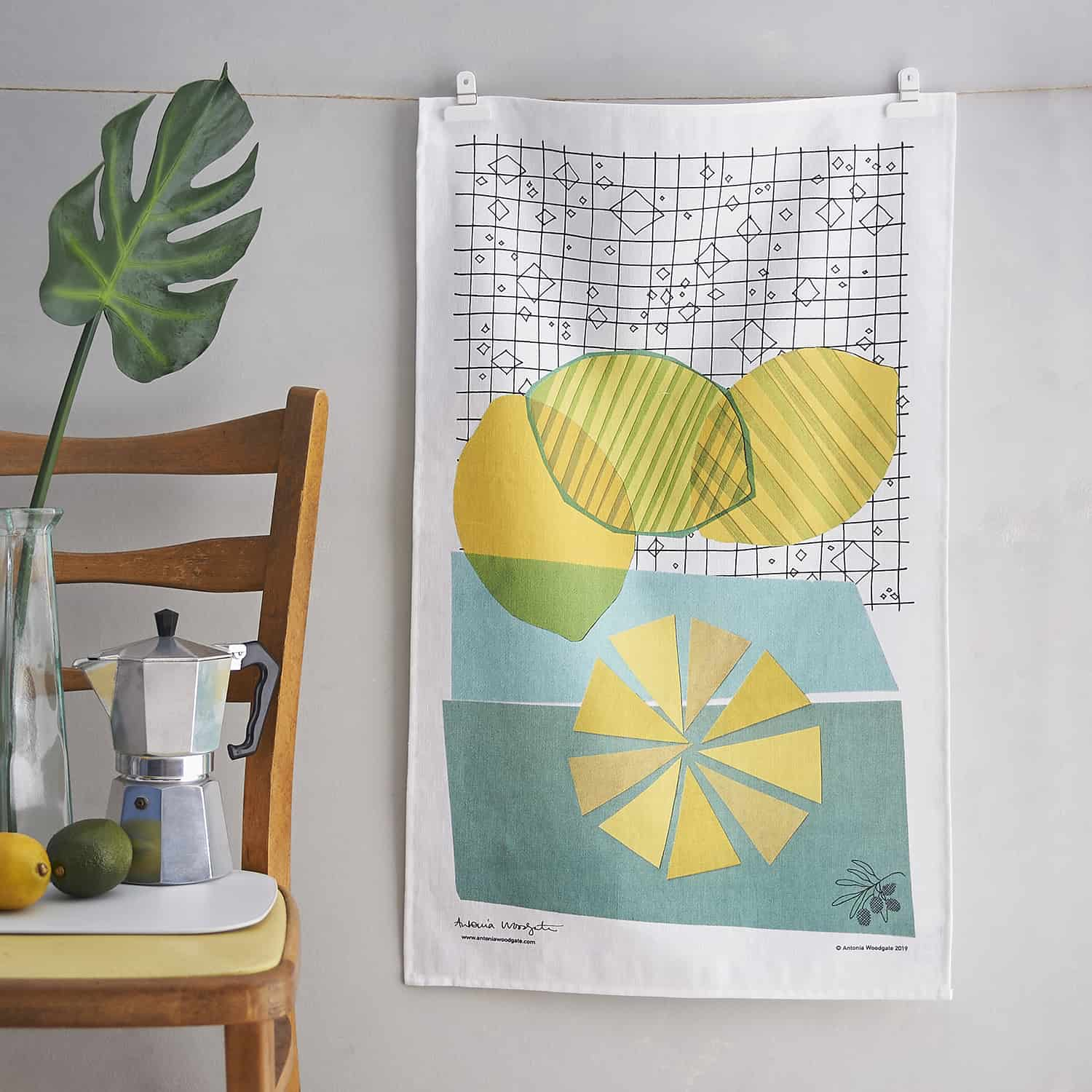 A photograph of a tea towel by designer Antonia Woodgate, styled with colour co-ordinating palm and fruits