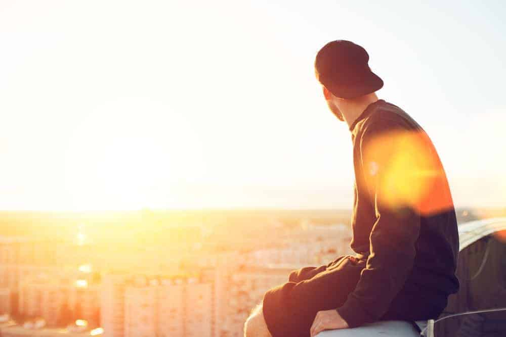 A man meditating on whether he should commit to recovery today. He is seated on a building roof overlooking New York City